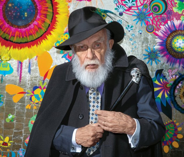 James Randi in front of a painting done by his partner, the artist José Alvarez. Credit Jeff Minton for The New York Times